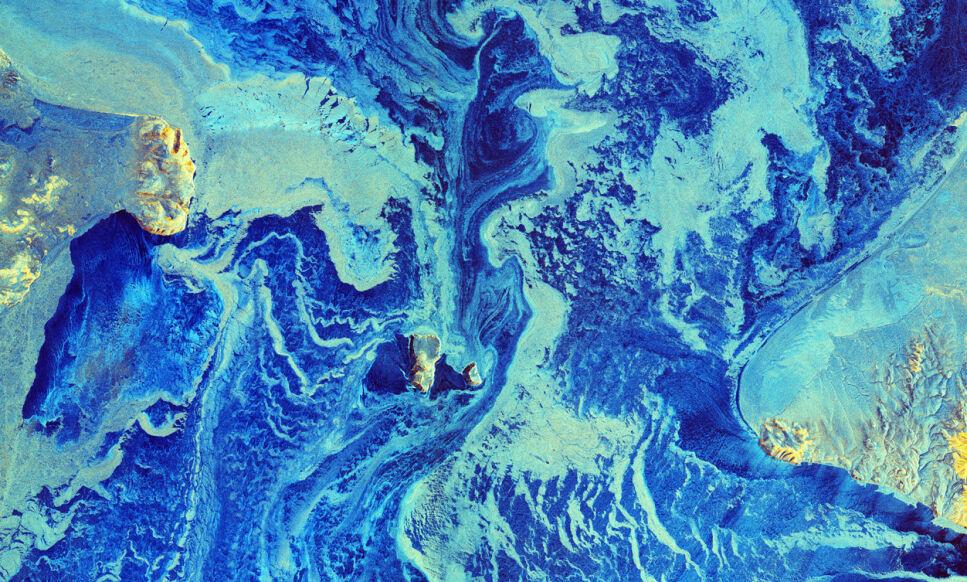 VARMERE: Dette satellittbildet av Beringstredet mellom Russland og Alaska fra mars i år viser et området som normalt er dekket av is på den årstiden. Det bildet viser er imidlertid et enormt isfritt område mellom Russland og USA, trolig som følge av varmere temperaturer og flere stormer. Foto: ESA
