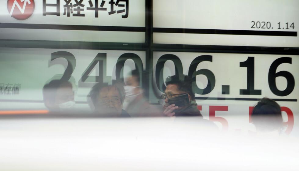 OPP: Aksjene på Tokyo-børsen styrket seg fredag etter at børsen i New York avsluttet med handelsrekord torsdag. Foto: Eugene Hoshiko / AP / NTB scanpix