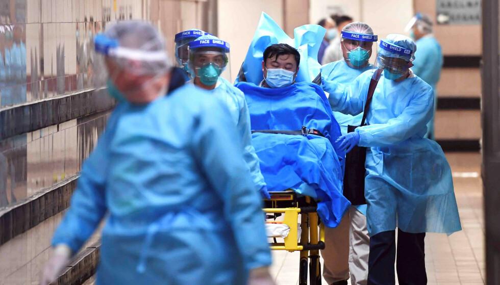 <strong>FRYKT:</strong> Medisinsk personell ved Queen Elizabeth Hospital i Hong Kong transporterer en pasient som kan være smittet med corona-viruset. Foto: cnsphoto via REUTERS.