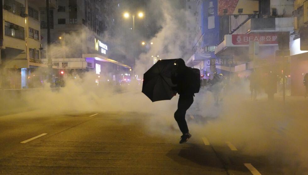 RAMMES HARDT: En demonstrant under et sammenstøt med politiet i Hongkong i begynnelsen av januar. Demonstrasjoner er blant faktorene som har rammet økonomien i landet hardt. Foto: Vincent Yu / AP / NTB scanpix