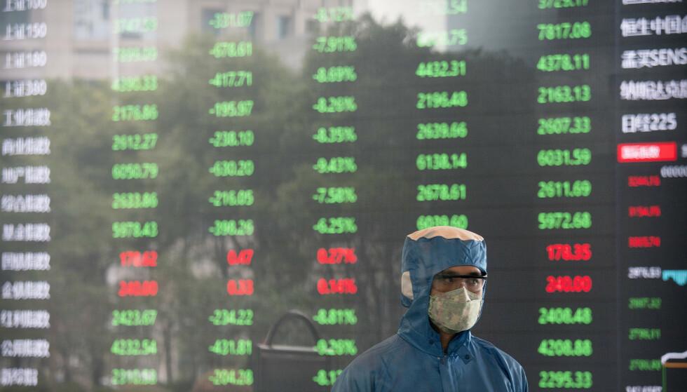 VIRUSFRYKT: En ansatt med ansiktsmaske og drakt på Shanghai-børsen tirsdag. Foto: AP / NTB scanpix