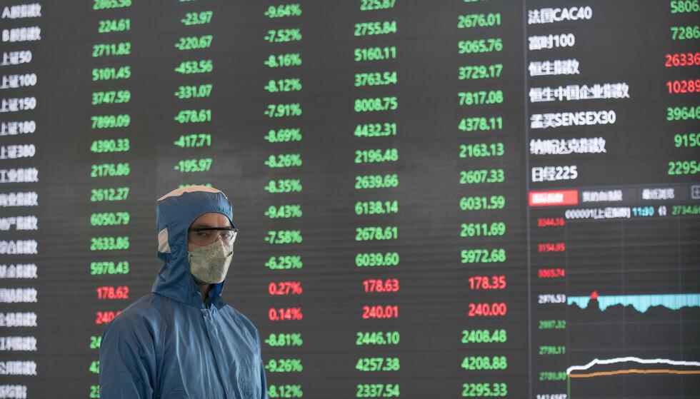 En ansatt med ansiktsmaske og drakt på Shanghai-børsen mandag. Foto: AP / NTB scanpix