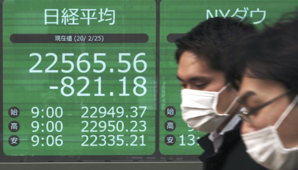 <strong>FALL:</strong> Fotgjengere passerer en tavle som viser utviklingen på Nikkei 225-indeksen i Tokyo tirsdag. Frykt for konsekvensene av utbruddet av covid-19-viruset sendte indeksen ned. Foto: Eugene Hoshiko / AP / NTB scanpix