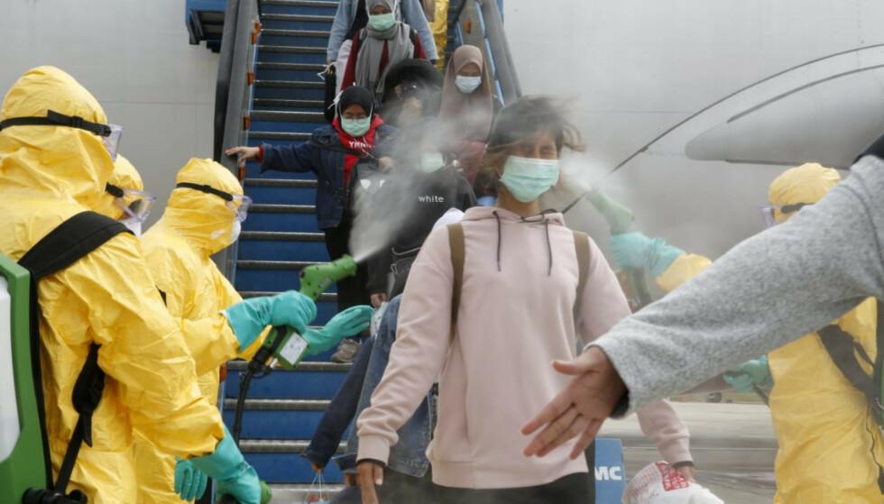 STORE RINGVIRKNINGER: Indonesiske flypassasjerer sprayes etter å ha ankommet fra Wuhan, hvor coronaviruset oppsto. Nå kan viruset påvirke det norske lønnsoppgjøret. Foto: Antara Foto/via Reuters / NTB Scanpix