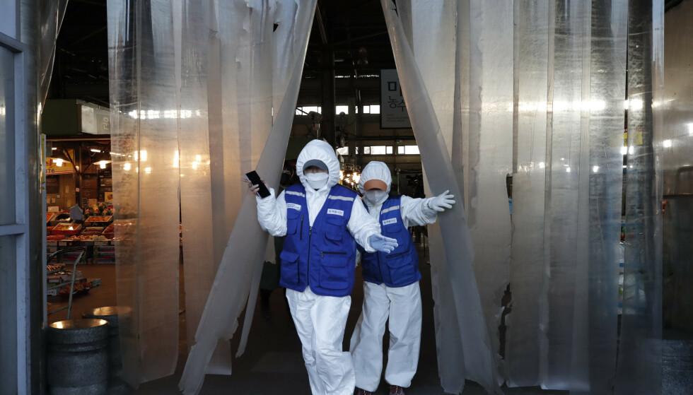 SYNKER: Frykten for konsekvensene av virusutbruddet førte til nok en dag med nedgang på børsene i Asia. Her er arbeidere på vei inn for å desinfisere et marked i Sør-Koreas hovedstad Seoul. Foto: Lee Jin-man/ AP/ NTB scanpix