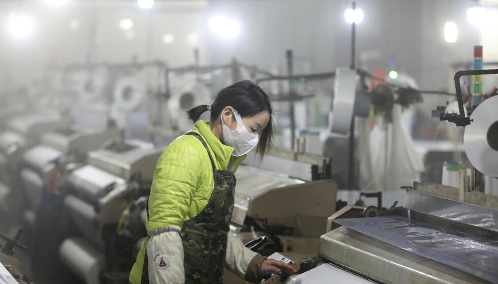 LAV VEKST: En kvinne med ansiktsmaske på en tekstilfabrikk i Hangzhou i den kinesiske provinsen Zhejiang i slutten av februar. Flere fabrikker i Kina har vært stengt som følge av coronaviruset. Foto: Chinatopix / AP / NTB scanpix