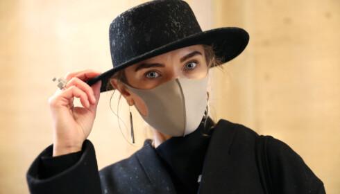 ANSIKTSMASKE: De moteinteresserte droppet ikke London Fashion Week, men stilte i stedet iført ansiktsmasker. Foto: Isabel Infantes / NTB Scanpix