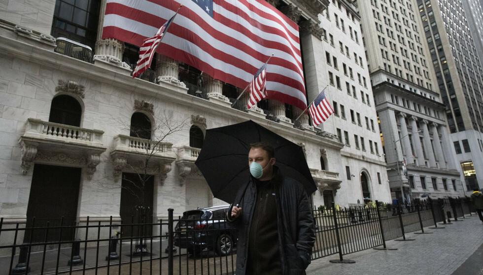 VIRUSFRYKT: Denne mannen hadde utstyrt seg med paraply mot regnet og maske mot smitte da han spaserte forbi børsen i hjertet av New Yorks finansdistrikt tirsdag morgen. Foto: Mark Lennihan / AP / NTB scanpix