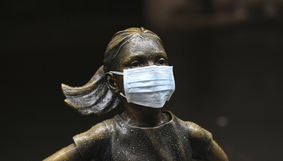 VIRUSFRYKT: Markedene i USA har den siste tiden vært svært ustabile. Annsiktsmasken som er plassert på den kjente statuen av den uredde jenta på Wall Street gir et tydelig hint om hvorfor. Foto: Kevin Hagen / AP / NTB Scanpix