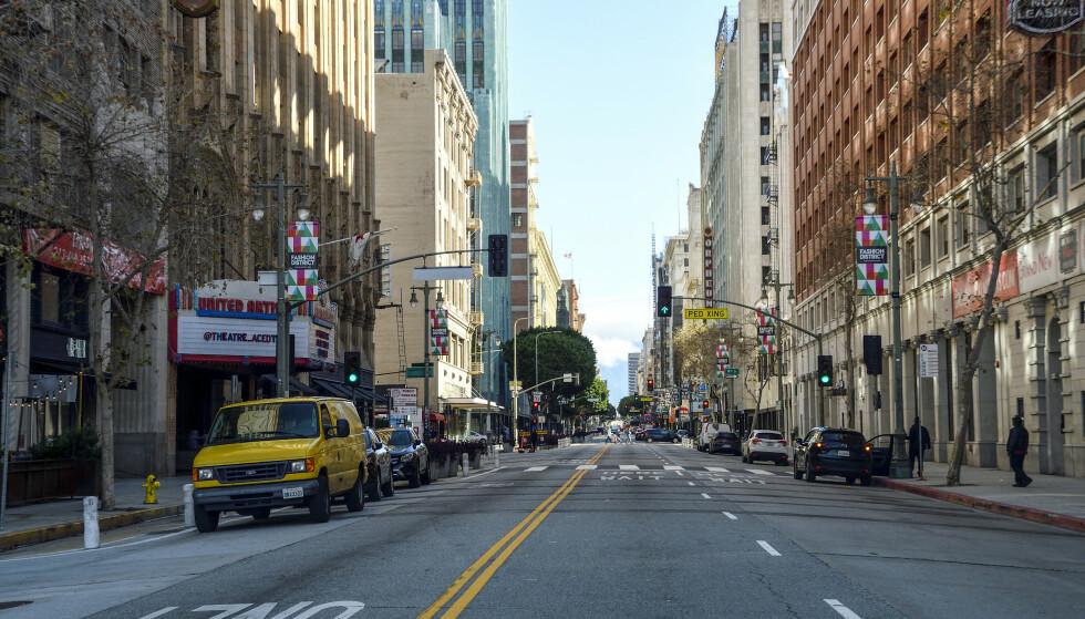 LITE FOLK: Broadway er vanligvis full av mennesker, men fredag 20. mars var det nesten tomt i sentrum av Los Angeles. Coronaviruset har nå sendt rekordmange ut i arbeidsledighet. Foto: Jeff Gritchen / The Orange County Register / SCNG via AP / NTB Scanpix