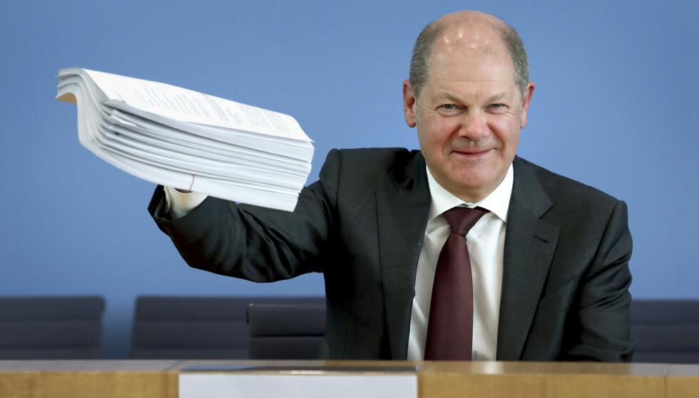 NEDGANG: Finansminister Olaf Scholz holder opp en bunke lovvedtak som inngår i den tyske regjeringens økonomiske krisepakke. Til tross for tiltakene spår tyske økonomer en økonomisk nedgang, og sier den er uunngåelig. Foto: Michael Sohn / AP / NTB scanpix