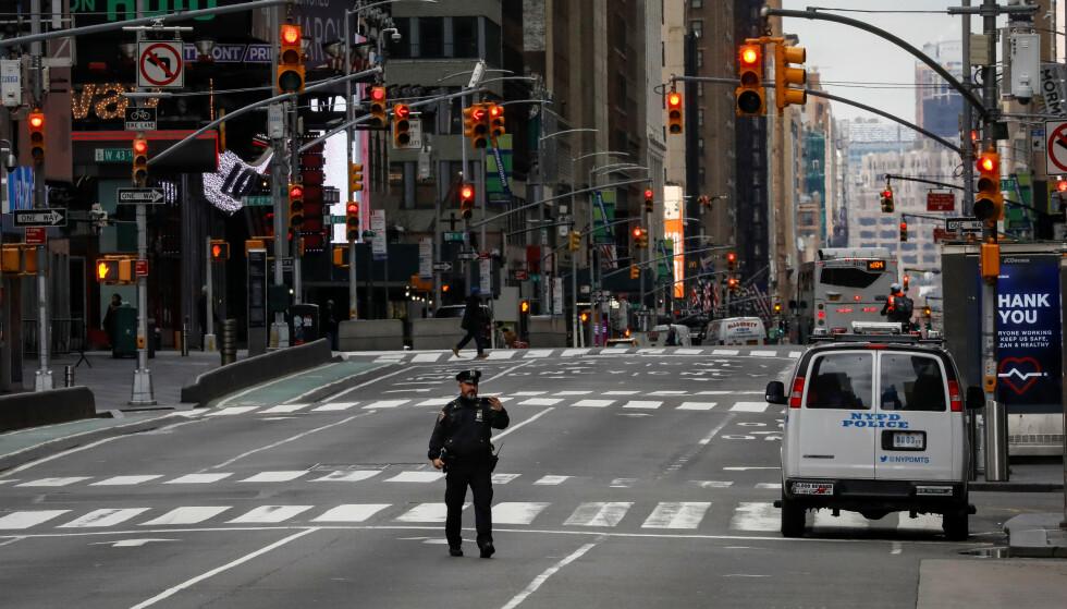 SJOKKTALL: Statistikk over arbeidsledighet og etablering av nye arbeidsplasser ble lagt fram i USA torsdag. Tallene var sjokkerende. Bildet viser en politimann i de folketomme gatene ved Times Square i New York. Foto: Brendan McDermid / Reuters / NTB Scanpix