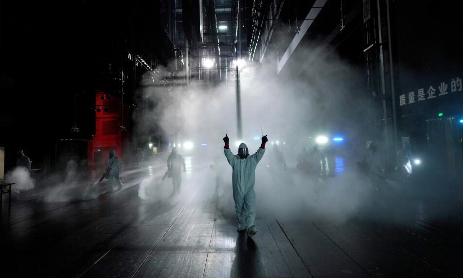 <strong>PÅVIST:</strong> Det var i byen Wuhan, med sine 11 millioner innbyggere, at coronaviruset først ble påvist. Bildet viser frivillige fra Blue Sky Rescue team som desinfiseres ved Qintai-teateret i Wuhan. Foto: Aly Song / Reuters / NTB Scanpix