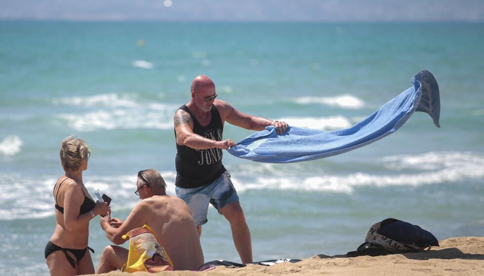 STRANDLIV: Tyske turister slenger seg ned på stranda i Palma de Mallorca i Spania mandag. Foto: Joan Mateu / AP / NTB Scanpix