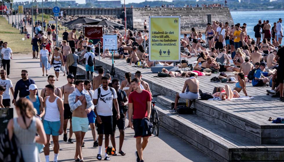 «HOLD AVSTAND»: Et skilt på en folksom badeplass i Malmö oppfordrer til å holde avstand. Bildet er tatt torsdag i forrige uke. Foto: Johan Nilsson / TT News Agency / REUTERS / NTB scanpix