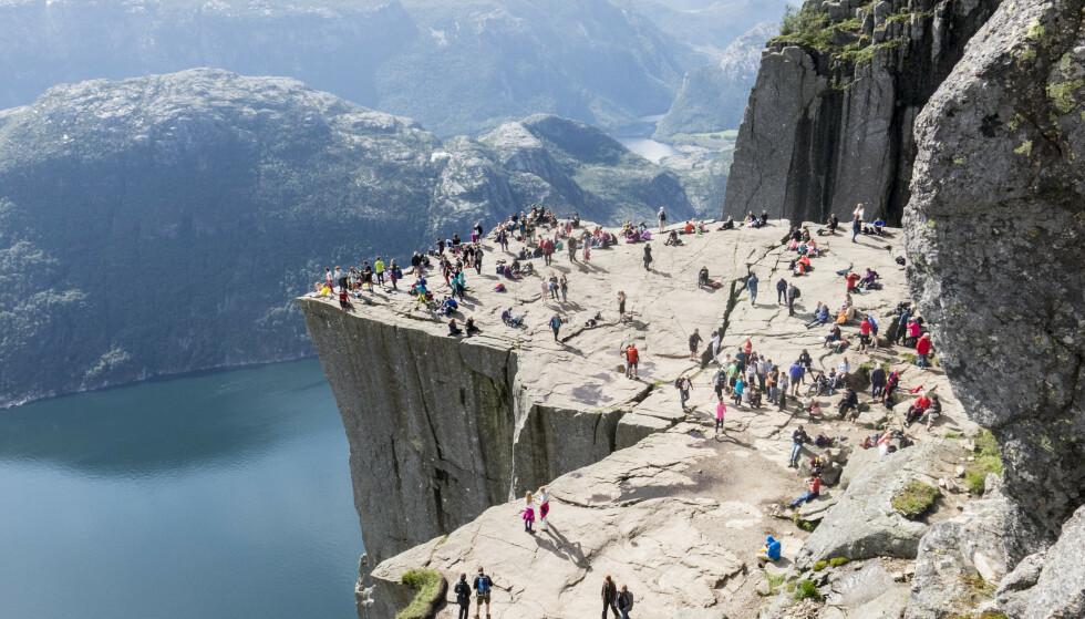 POPULÆRT TURISTMÅL: Turister strømmet i fjor til Preikestolen ved Lysefjorden. En ny undersøkelse viser at mange nordmenn ikke ønsker besøk av utenlandske turister i sommer. Foto: Paul Kleiven / NTB Scanpix