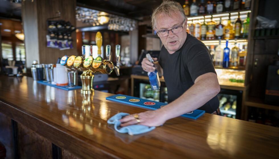 HALDEN: Tidligere FrP-politiker Per Sandberg rengjør bardisken før åpningen av puben Grand Bar i Halden. Foto: Heiko Junge / NTB scanpix