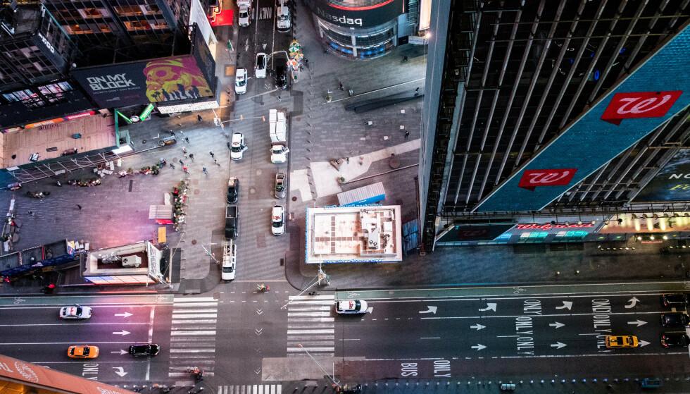 SLÅR ALARM: Bildet viser et nært folketomt Times Square i New York 18. mars i år. Coronapandemien og de medfølgende nedstengningene av samfunn over hele verden, har ført til en enorm smell for verdensøkonomien. Nå slår næringslivsledere fra hele verden alarm. Foto: Jeenah Moon / Reuters / NTB