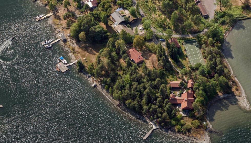 STOR BOLTREPLASS: Fire søsken i Knappskog-familien gikk for få måneder siden til innkjøp av nabotomta til barndomshjemmet. Sistnevnte eiendom er plassert ytterst på øya (med tennisbane). Milliardærarvingene har kjøpt første bolig til venstre for barndomshjemmet (oransje tak). Foto: 2020 Norkart AS / Geovekst og kommunene / OpenStreetMap / NASA, Meti