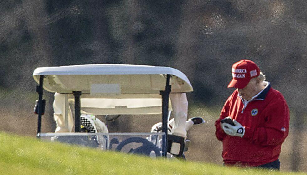 SPILLER GOLF: USAs president, Donald Trump, på telefonen under en golfrunde på sin egen golfbane i Virginia 26. november. Foto: Tasos Katopodis/Getty Images/AFP