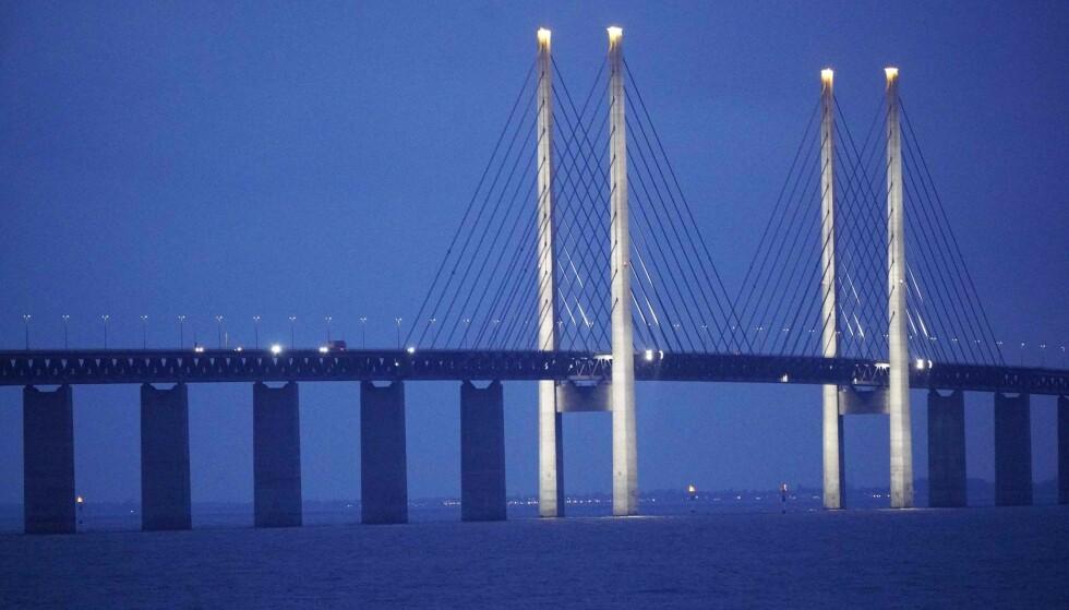 MØRKT: Øresundbroen mellom Sverige og Danmark lyses opp i kveldsmørket. Våre naboer ser også langt lysere på sine hjemlands framtidsutsikter enn vi nordmenn. Foto: Johan Nilsson / TT / AFP / NTB