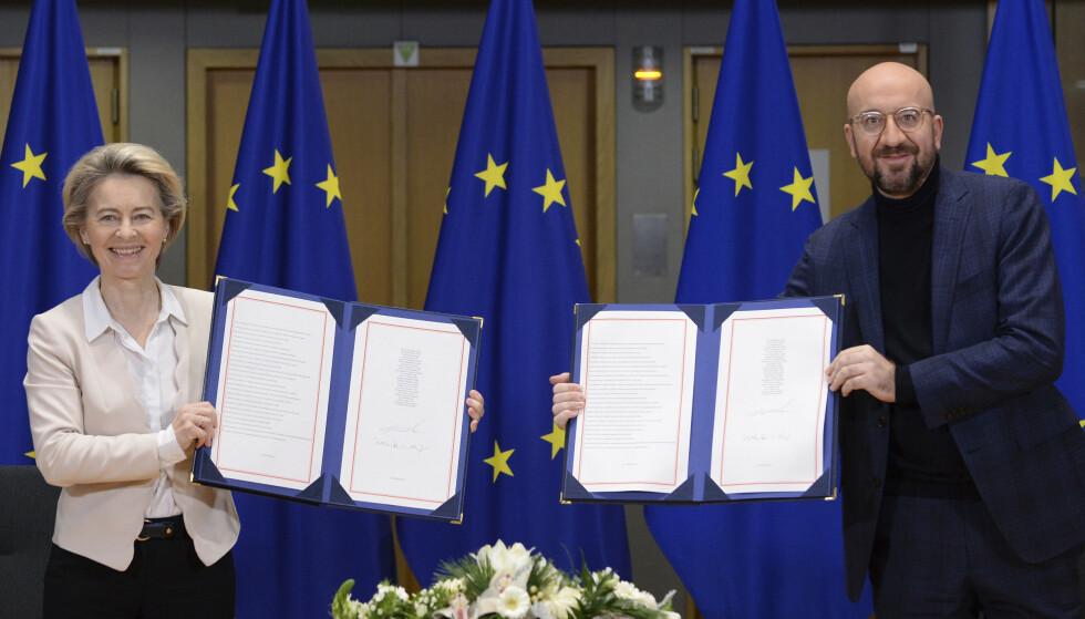 EU-kommisjonens leder Ursula von der Leyen og EU-president Charles Michel viser fram brexitavtalen som ble undertegnet i Brussel onsdag morgen. Avtaledokumentet ble deretter brakt til London med fly. Foto: Johanna Geron / AP / NTB