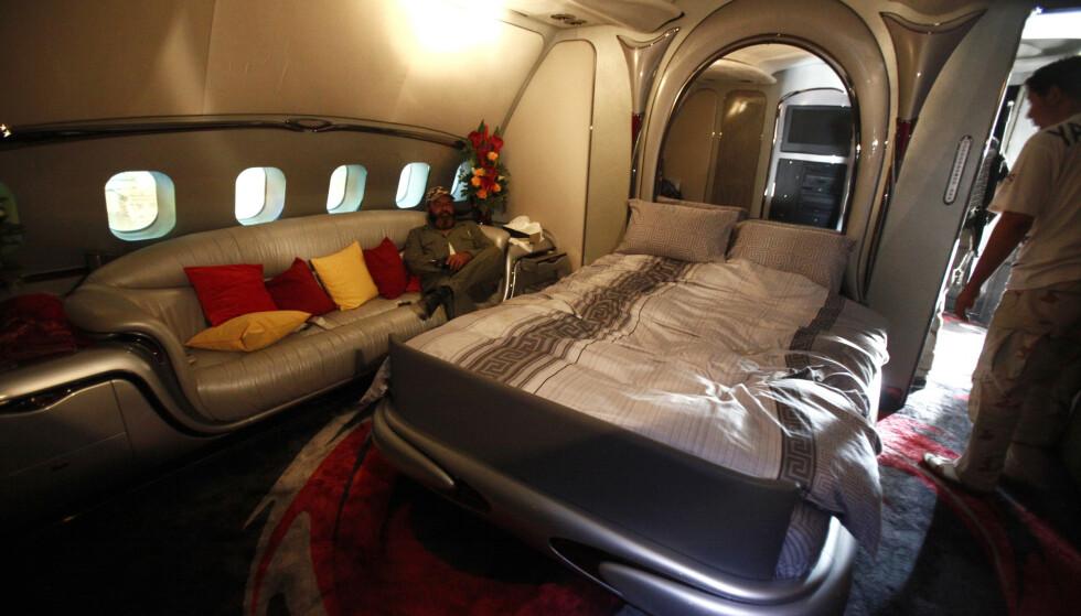 FLYSENG: En opprører viser fram Gadaffis soverom ombord. Flyets seng har en speildekket sengegavl. Foto: Zohra Bensemra / Reuters