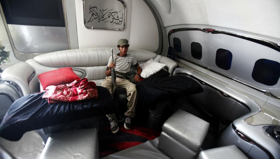TATT OVER: En opprører poserer med et gevær, inne i Gadaffis luksusfly. Foto: Zohra Bensemra / Reuters