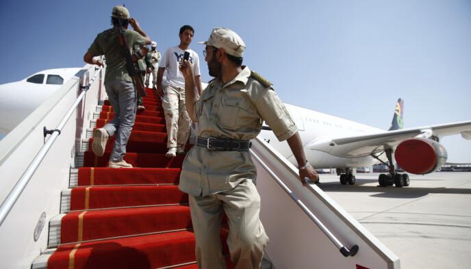 LUKSUSFLY: En libysk opprørssoldat tar et bilde av Muammar Gaddafis private fly med mobiltelefonen sin på den internasjonale flyplassen i Tripoli, 28. august 2011. Foto: Zohra Bensemra / Reuters