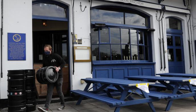 Puber og restauranter får åpne igjen med utendørsservering mandag i England. Folk må bestille og drikke fra bordene. Foto: Frank Augstein / AP / NTB