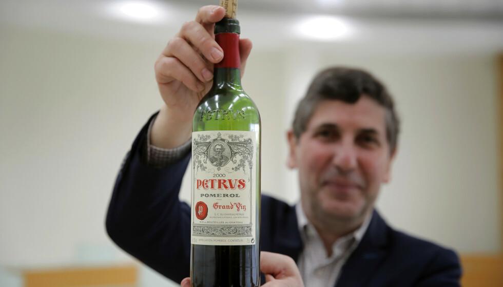 EKSKLUSIV: Sjef for vininstituttet (ISVV) ved Universitetet i Bordeaux, Philippe Darriet, holder opp en flaske av Pétrus, som ble lagret i verdensrommet. Foto: AP Photo/Christophe Ena