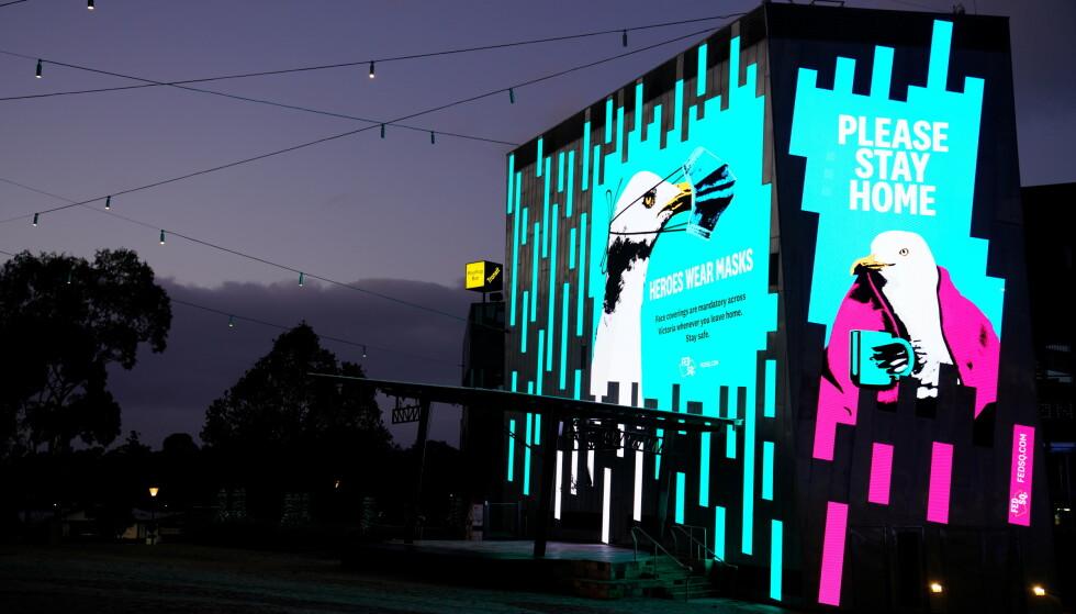 """NATT OG TOMT i Melbournes gater. Helsemyndighetene i den nedstengte storbyene har valgt måker som budbringere på store plakater og lystavler med budskapene """"Vær så snille - hold dere hjemme"""" og """"Helter bruker munnbind"""". Flyselskapet Qantas lanserer en mer offensiv kampanje for å bevege seg til og fra Australia. Foto: Sandra Sanders, Reuters/NTB."""