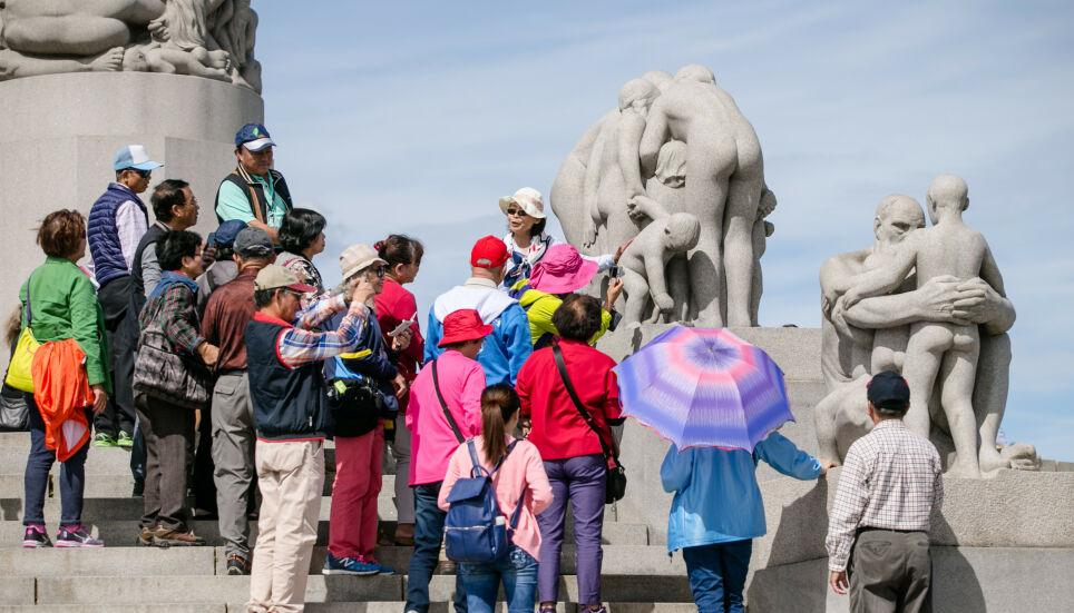 SJELDENT SYN: En gruppe asiatiske turister studerer skulpturene ved «Monolitten» i Frognerparken og Vigelandsparken i Oslo i 2015. De siste 15 månedene har det vært langt mellom de utenlandske turistene i Norge. Foto: Audun Braastad / NTB