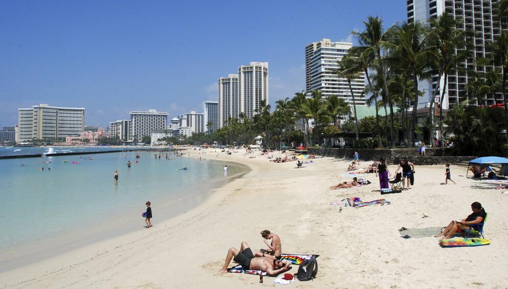 IKKE FORBEREDT: Ferieparadiset Hawaii er bekymret for turistsituasjonen. Her er turister avbildet på en strand i Honolulu i 2017 - før turisttallet var i ferd med å «sprenges». Foto: AP Photo / Caleb Jones