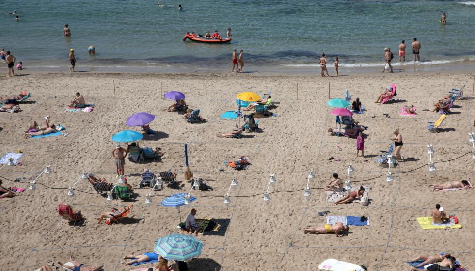JUNI 2021: Folk koser seg, med god avstand, på stranda i Benidorm. Foto: REUTERS/Eva Manez Lopez / NTB