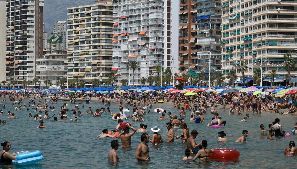 AUGUST 2018: Folk koser seg på stranda i Benidorm i Alicante. Foto: JOSE JORDAN / AFP