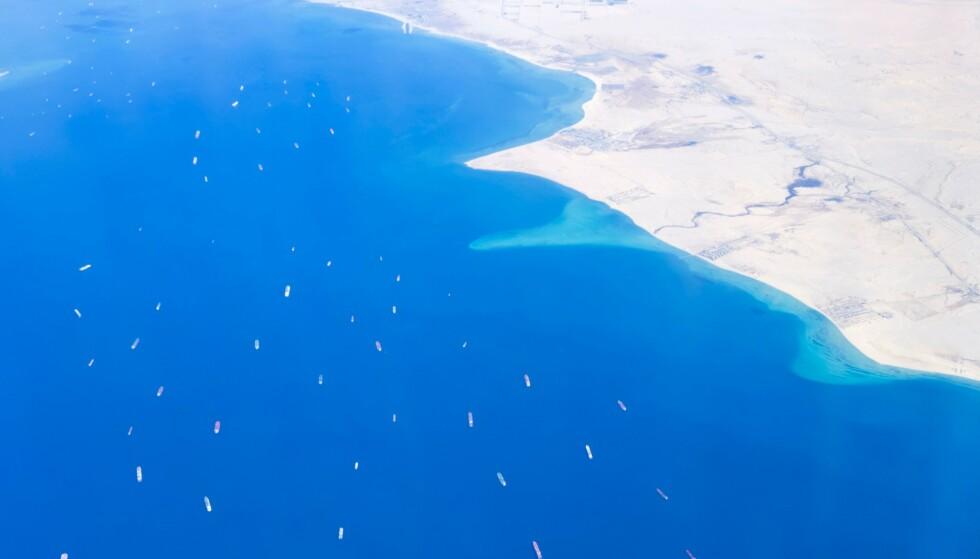 STORE KONSEKVENSER: Grunnstøtingen i Suezkanalen førte til store forsinkelser i den internasjonale handelen med dertil økonomiske konsekvenser. Bildet viser skip som venter i Rødehavet, mens slepebåter jobbet med å dra «Ever Given» av grunn. Foto: Mahmoud Khaled / AFP / NTB