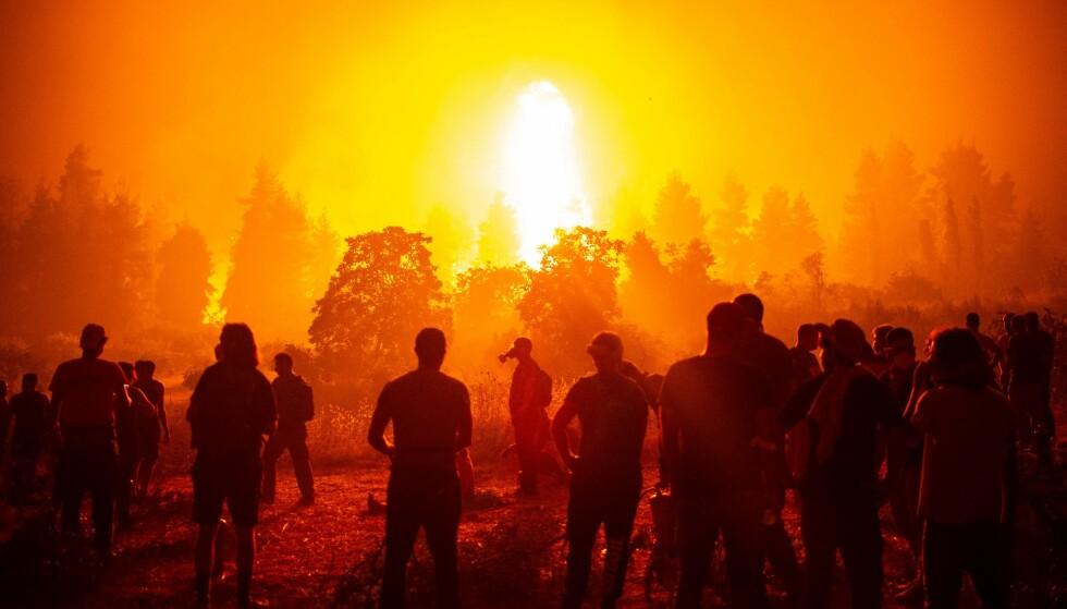 VERDEN I BRANN: Den voldsomme skogbtrannen på den greske øya Evia har tatt flere hundre bygninger og forårsaket apokalyptiske scener. Her samler folk seg på en åpen plass mandag for å bistå brannmannskapene som frivillige. Foto: Angelos Tzortzins, AFP / NTB