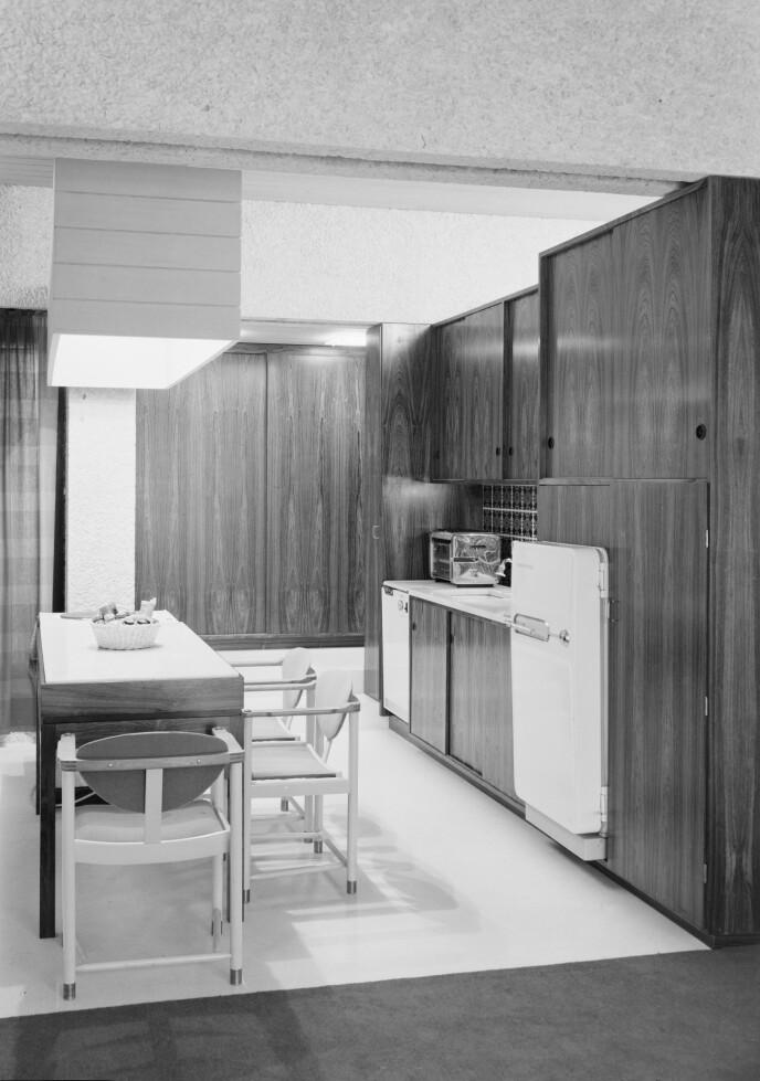 OPPRINNELIG KJØKKEN: Byvillaen er et unikt eksempel på 60-tallsarkitektur hvor bærende fasadekonstruksjoner og deler av innvendige vegger er utført i naturbetong, heter det i annonsen. Dette er et eldre interiørbilde. Foto: Teigens fotoatelier / Dextra Photo / Norsk Teknisk museum