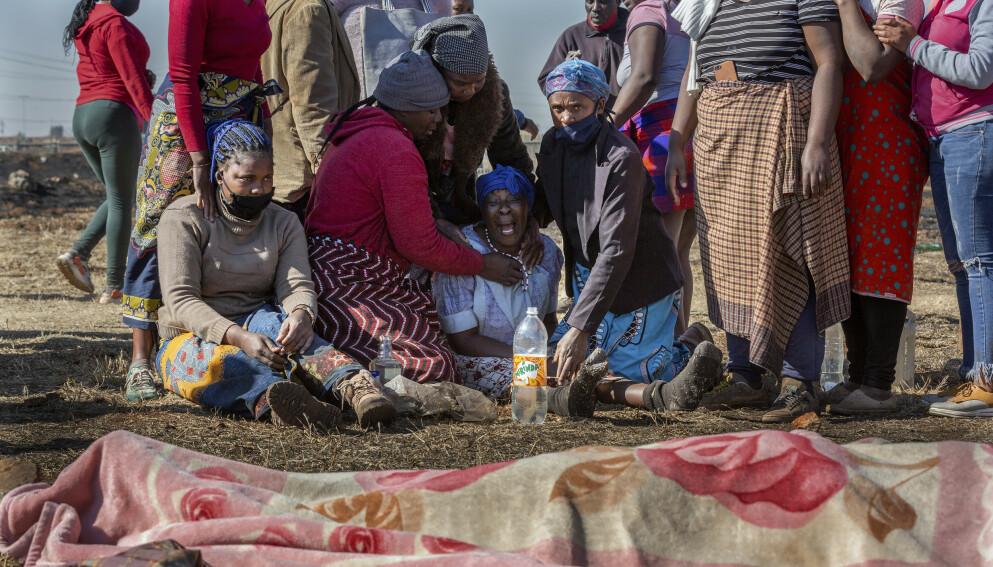 DREPT: Familiemedlemmer sørger ved en femten år gammel gutt som angivelig ble skutt og drept av medlemmer av et taxiselskap. Foto: AP Photo/Yeshiel Panchia/NTB