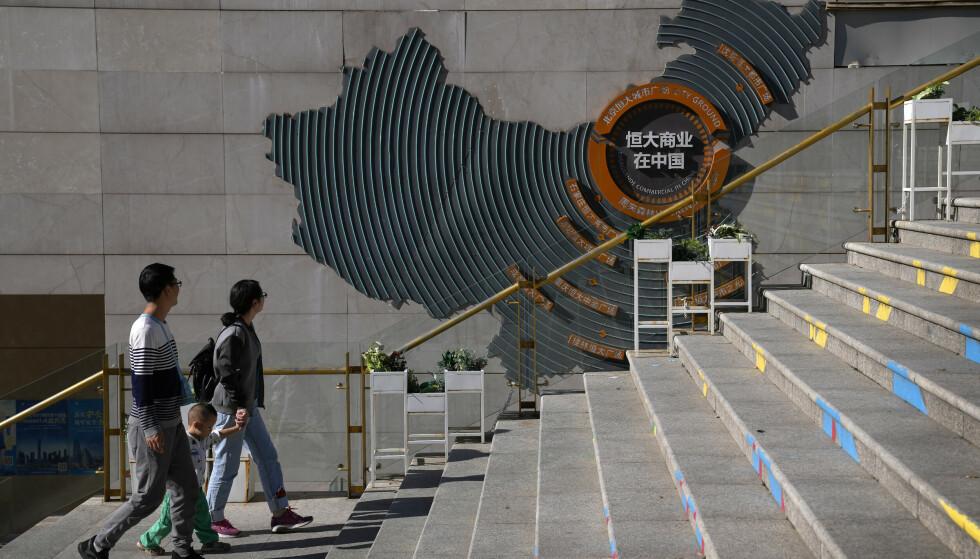 ENORMT: En kinesisk familie går forbi et stort kart på veggen som viser Evergrandes enorme utviklingsprosjekter og bygårder i Beijing. Globale investorer følger nervøst med på dramaet rundt Evergrande Group, en av Kinas største eiendomsutviklere, som nå er truet av konkurs. Foto: AP/NTB