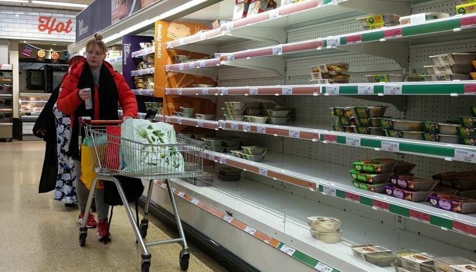 TOMME HYLLER: En kvinne handler blant tomme butikkhyller på et supermarked i Storbritannia. Venstre mener det samme kan skje her hjemme. Foto: Dinendra Haria/LNP/Shutterstock