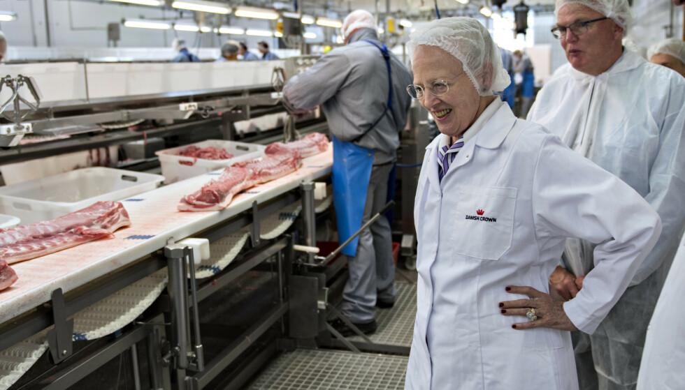 TAR GREP: Danish Crown - som blant annet har en sterk markedsposisjon på salg av bacon til Norge - varsler forandring. Avbildet er danske dronning Margrethe på besøk ved et av selskapets slakterier i 2017. Foto: Keld Navntoft / NTB